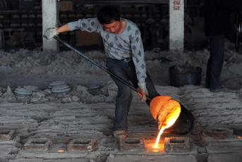 A Chinese worker pours molten steel into the casters at a small iron and steel mill in Hefei, central China's Anhui province on June 19, 2010. China, the world's leading iron ore consumer, saw imports surged 41.6 percent to 627.8 million tonnes in 2009 on soaring demand from steel mills. CHINA OUT AFP PHOTO (Photo credit should read STR/AFP/Getty Images)